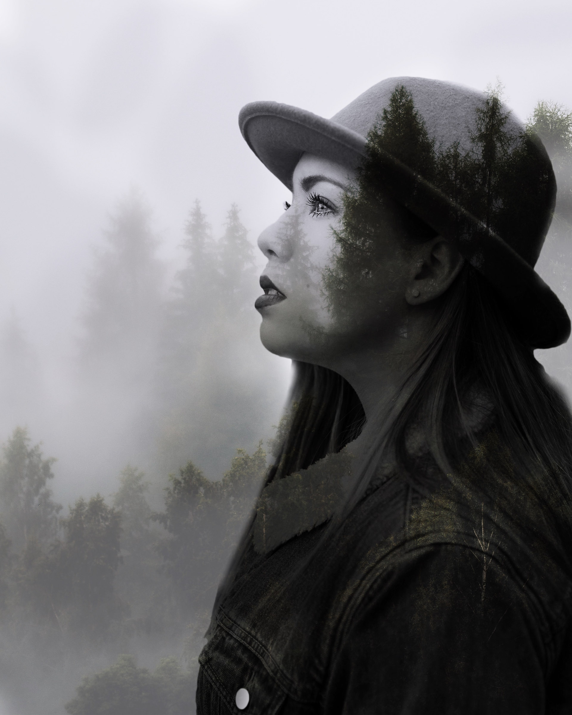 Woman in profile with a double exposure of pine trees