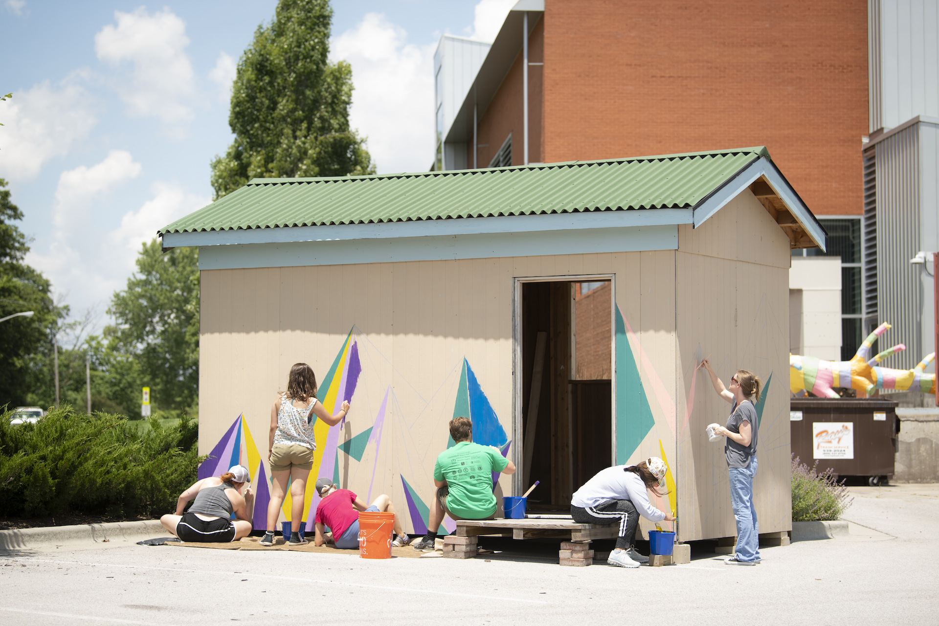 Students painting the side of the plastic shred shed