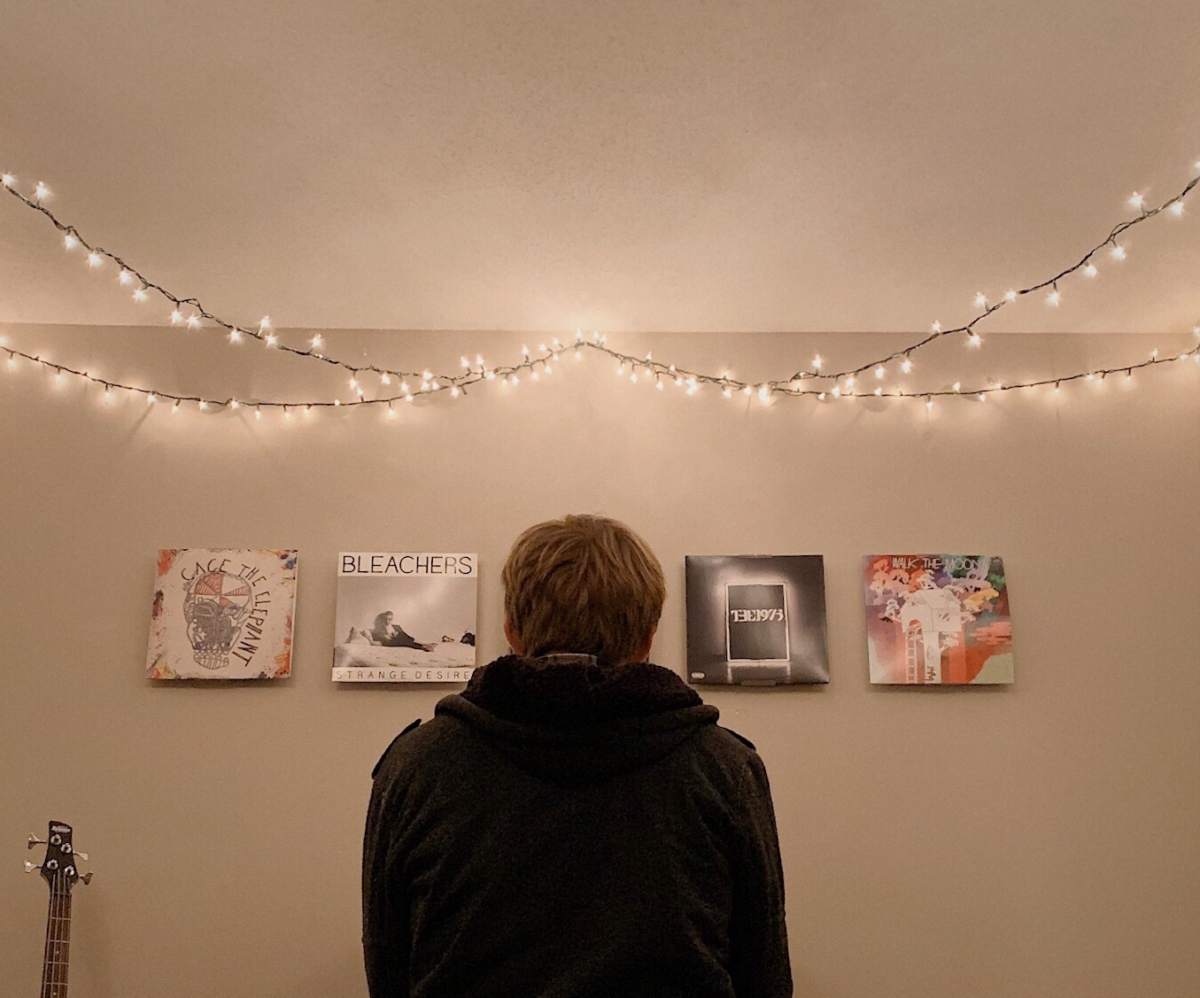 Person viewing four photographs beneath strings of Christmas lights