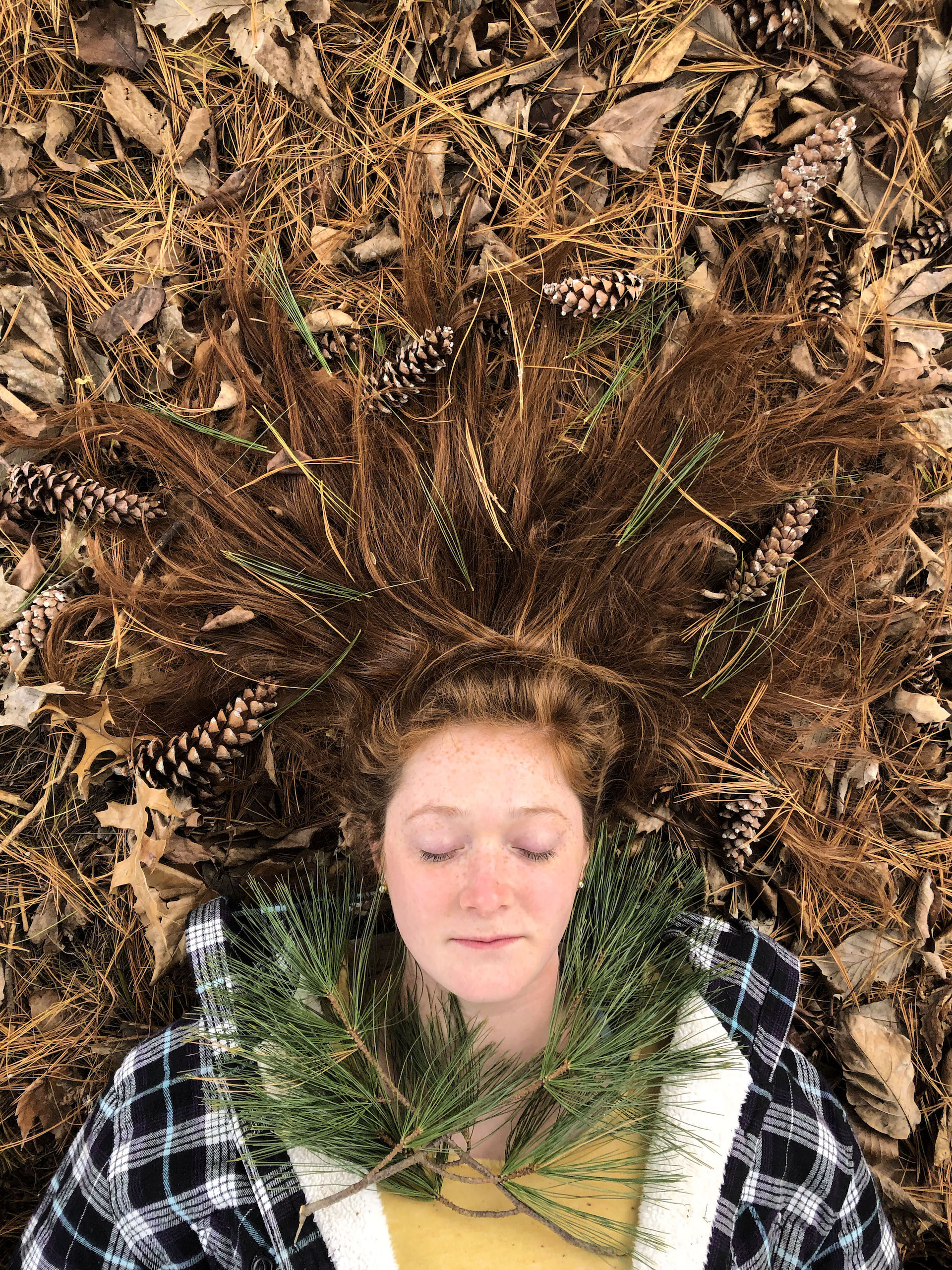 Woman lying on a bed of pine needles