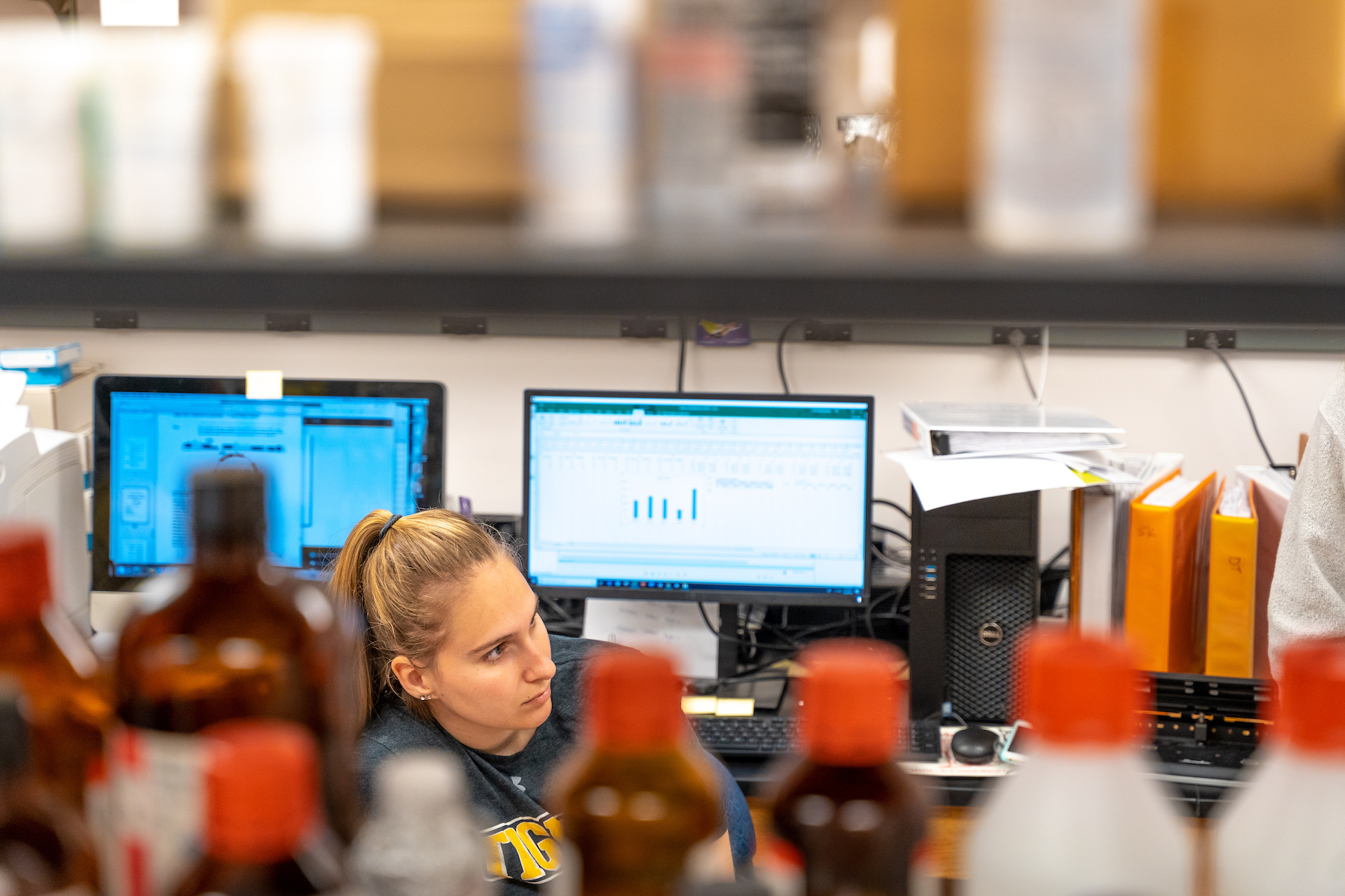 Student sitting behind some bottles during summer research