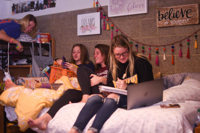 Three female students sitting on a bed with computers.