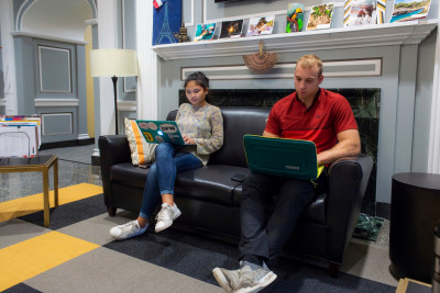 Two students sitting on a couch with laptops in the Hubbard Center for Student Engagement