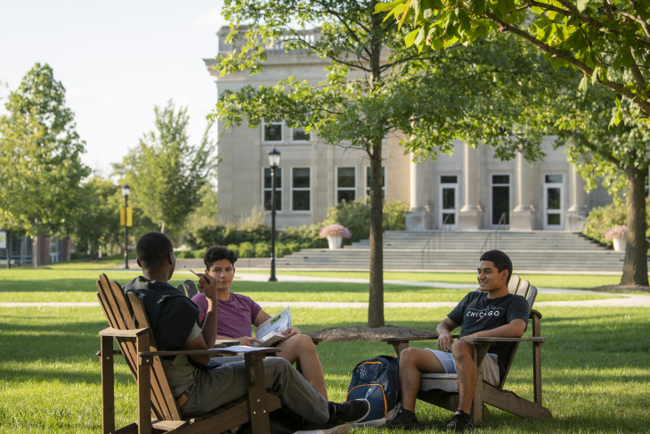 Students sitting on the East College lawn with Emison building in the background