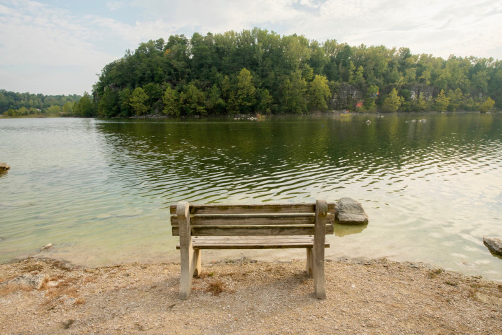 An empty bench in front of an expanse of water in the DePauw Nature Park