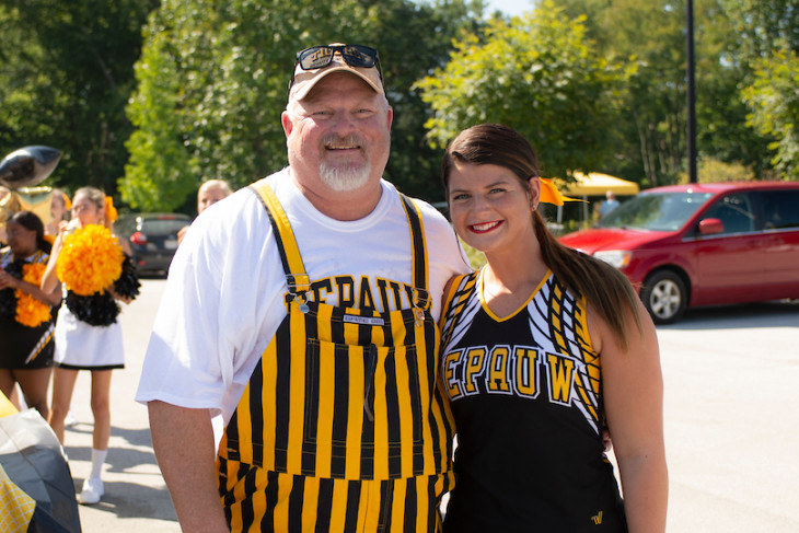 a cheerleader and her dad stand and smile during tailgating
