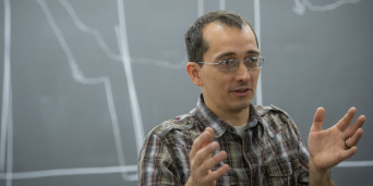 Dr. Jacob Hale teaching a class with chalkboard in the background