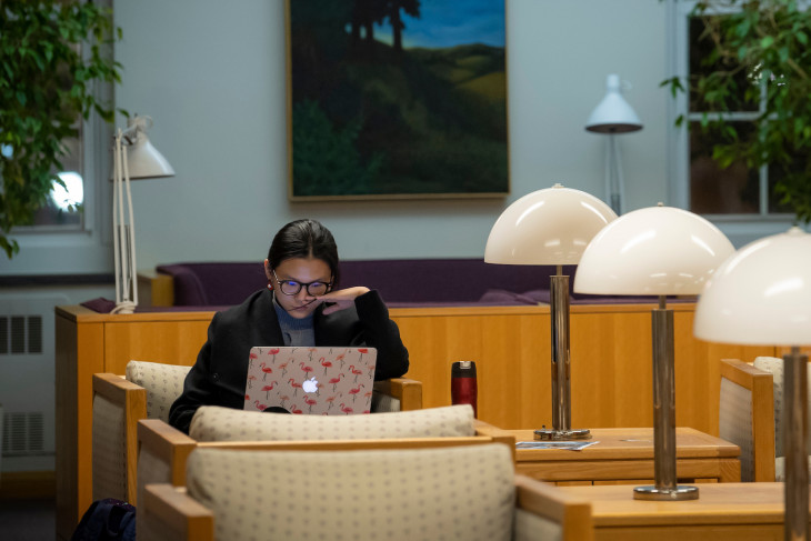 student writing and studying in Roy O West Library