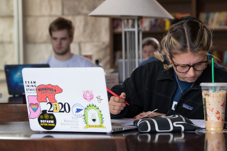 student sitting at a table with a coffee and a computer