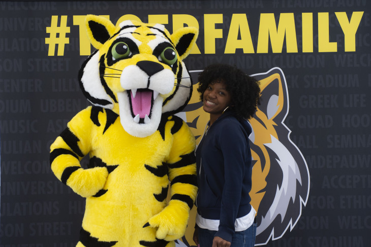 student and tyler the tiger stand in front of a sign that says #tigerfamily