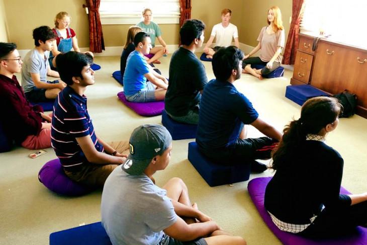 meditation club meeting. students sitting on yoga mats