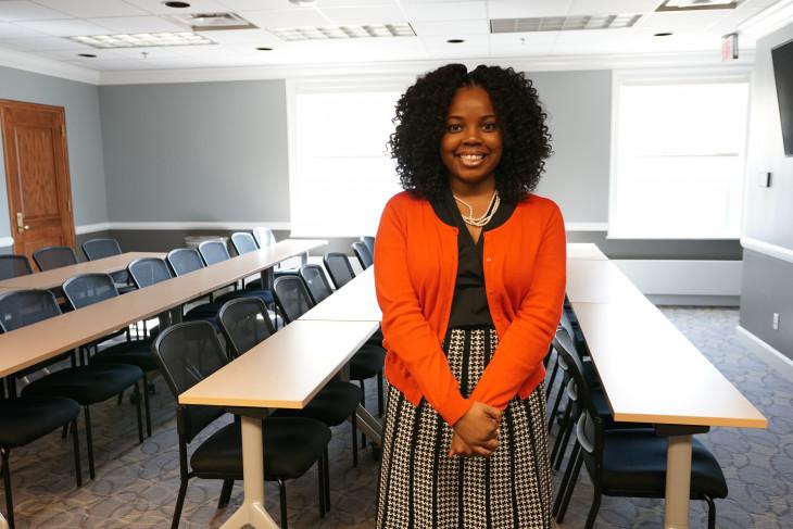 Nicole Burts '13 standing in a room full of desks