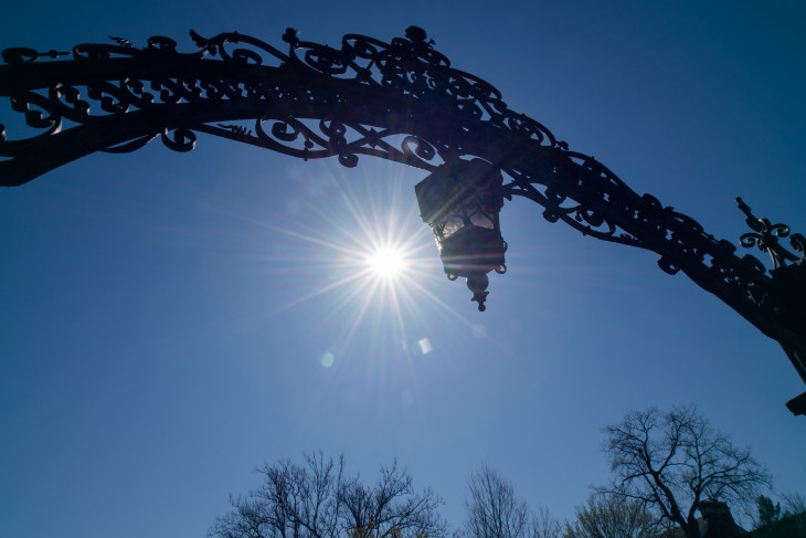 The sun glistens behind the arch.