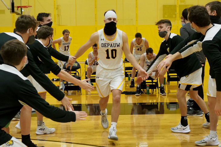 Masked basketball player runs into the game, greeted by teammates