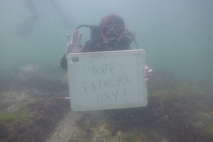 Caleb under water holding a sign that says happy fathers day