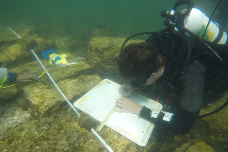 Caleb underwater marking on a white board and making measurements