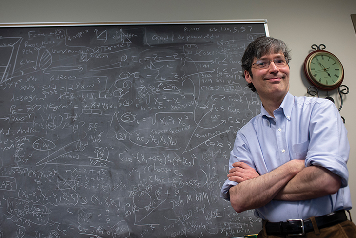 Alexander Komives stands before a chalkboard full of research data