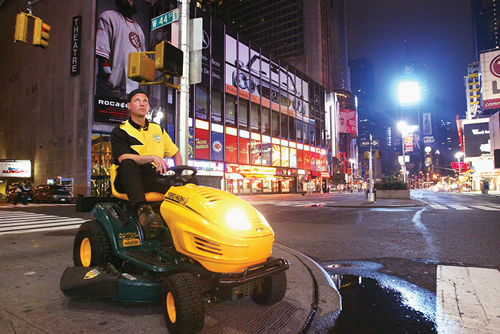 Brad Hauter '87 sitting on a lawn mower in a city street