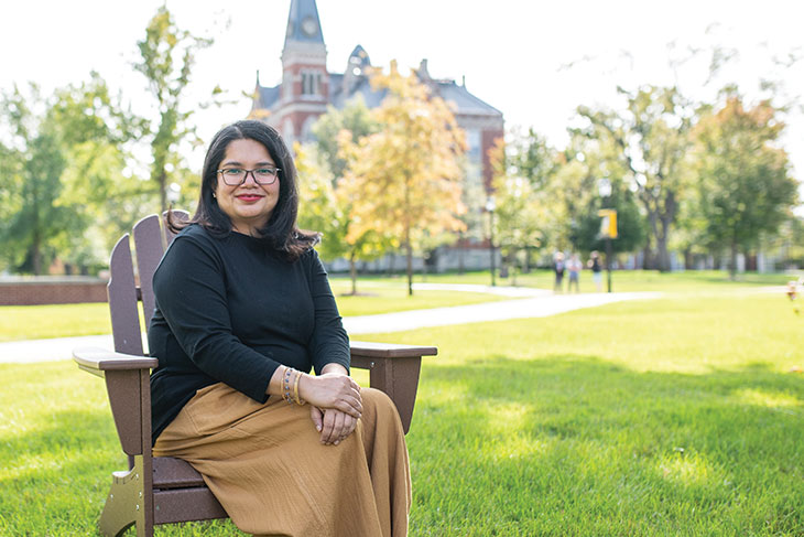 Deepa Prakash in an Adirondack chair in front of East College