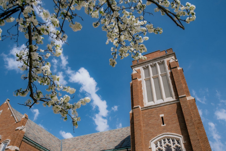 Vivid blue sky with apple blossoms in the foreground and a campus building in back