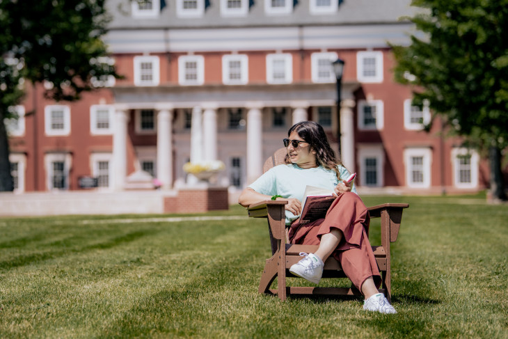 student sitting in an adirondack chair on east college lawn