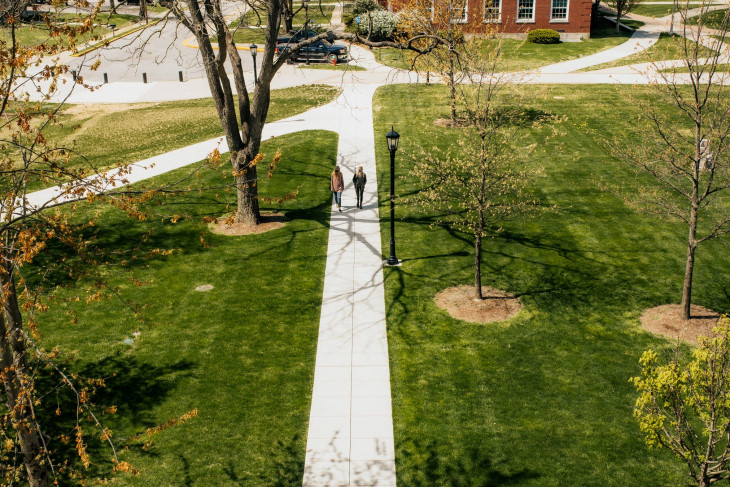 Two students walk along a sidewalk amidst budding trees on campus