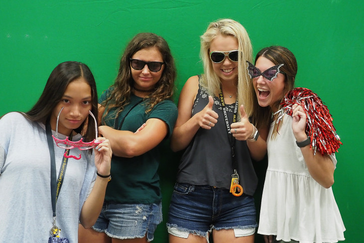 Students posing in front of a green screen