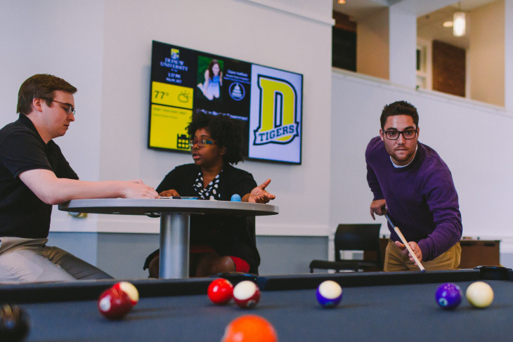 faculty and student talking at a table in front of a digital sign. student in foreground playing pool.