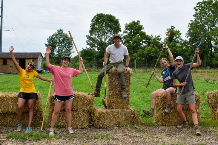 Students pose with digging tools atop hay that was laid down on farm grounds.