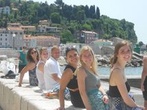 Students sitting on a concrete block along the water looking over their shoulders