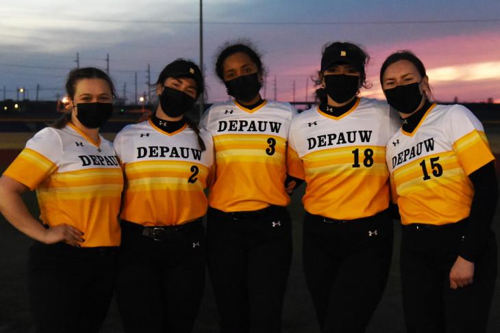 Masked softball players at dusk