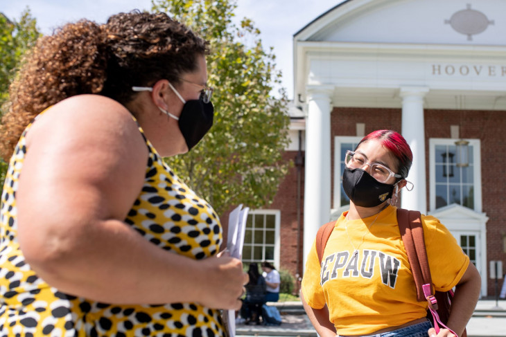 Masked student and staffer talk outside