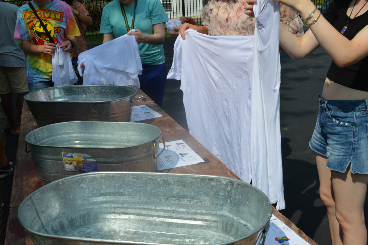 Group of students holding white shirts, in the process of tye-dying