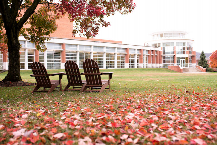 fall leaves and three chairs facing the Green Center