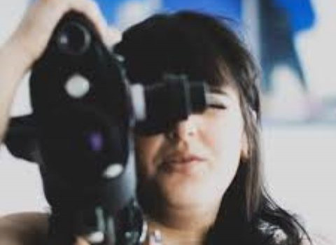 Akanksha Cruczynski behind a camera filming a scene