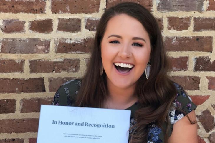 riley hawkins holds up her acceptance letter