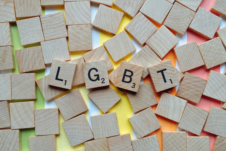 Scrabble pieces on a rainbow background, spelling out the letters LGBT