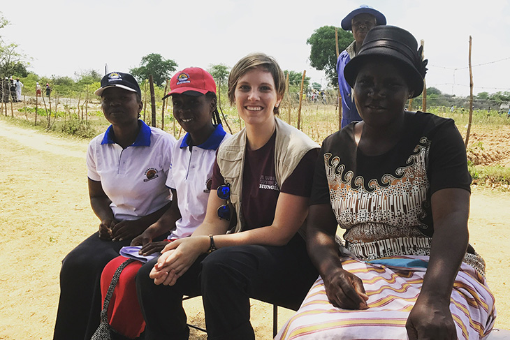 Ashley Baxstrom, third from left, between locals in Zimbabwe.