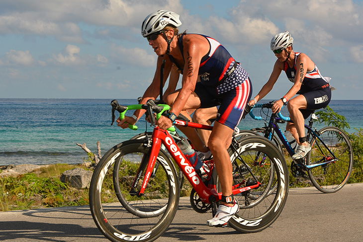Sue Engle Reynolds '76 competing on bicycle in a triathlon against the backdrop of a Cozumel ocean view