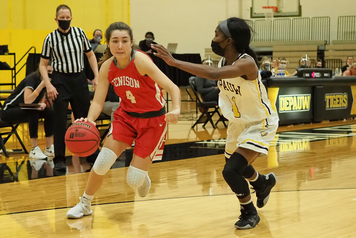Masked DePauw basketball player guards opponent