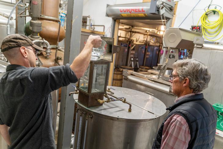 Pogue family pouring liquid into machine