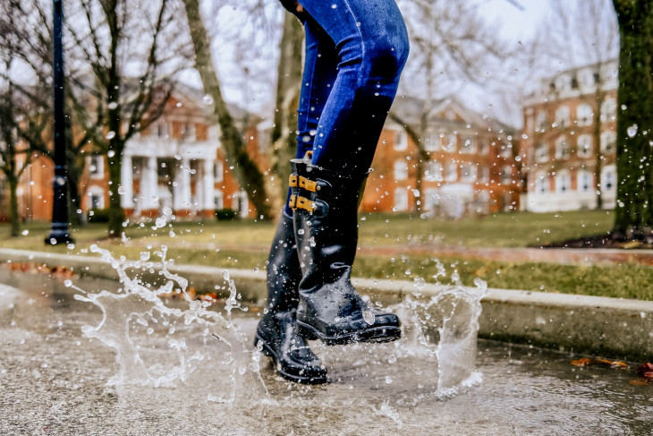 Feet stomping in puddles with campus buildings in the background.