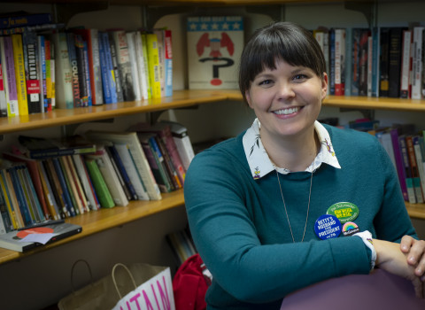 Sarah Rowley sitting in and office with books in the background
