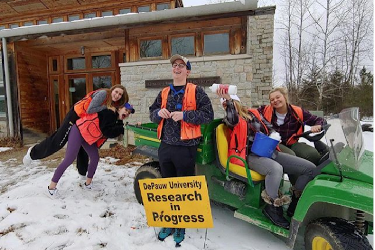 Students standing in snow with a sign that says research in progress