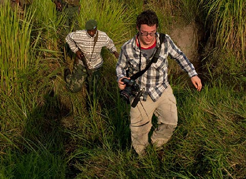 Ben Solomon '10 walking through tall grass while reporting in west Africa
