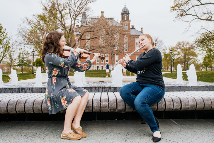 Music students playing in front of a water feature with East College in the background