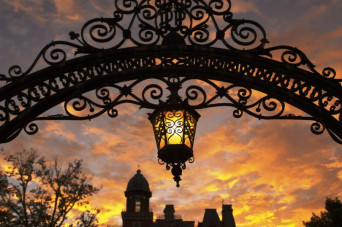 Arch with hanging lantern during sunset with East College backdrop