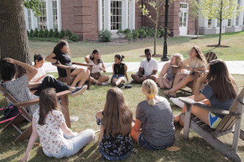 Students sitting in a circle for a class held outdoors
