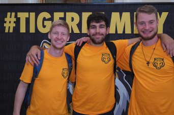 Three mentors standing in front of a #TigerFamily backdrop