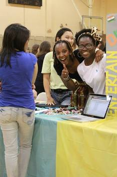 Students smiling behind their organization table at an event